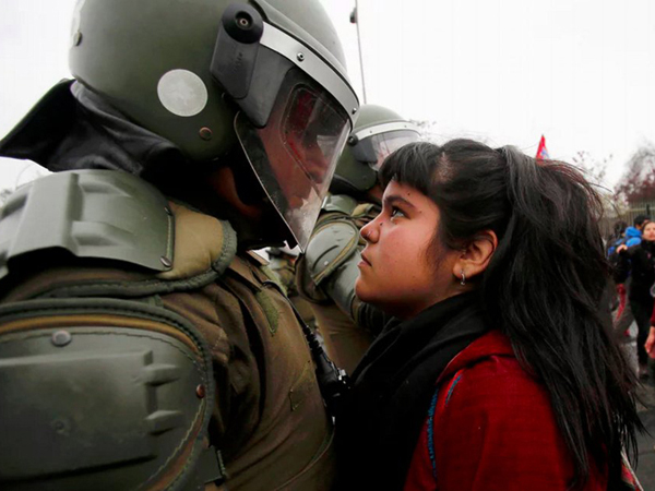 The young demonstrator locked eyes with a riot policeman during a pro democracy protest in Santiago, Chile